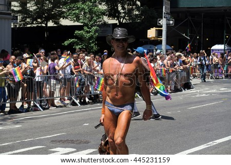 NEW YORK, NEW YORK - JULY 26, 2016: Man marching in Gay Pride Parade on 5th avenue. The rainbow flags are the symbol of lesbian, gay, bisexual and transgender pride and diversity. Editorial use only. - stock photo