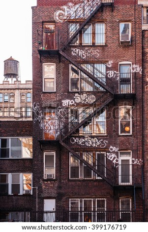 NEW YORK, NEW YORK - MAR 3:  Residential dwellings, with graffiti, in New York City, and also water tank atop the walk-up on March 3, 2012. Many of NYC's residential buildings are pre-war structures. - stock photo