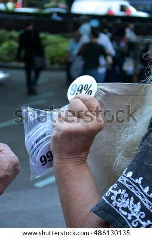 "New York, New York. - September 17, 2016: Woman handing out ""99%"" pins at Zuccotti Park in Lower Manhattan to mark the fifth anniversary of the Occupy Wall Street movement in 2016 in New York City"