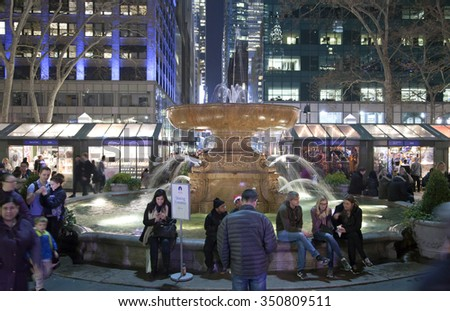 NEW YORK, NEW YORK, USA - DECEMBER 10: People sit near the fountain in Bryant Park.  Taken December 10, 2015 in NY. - stock photo