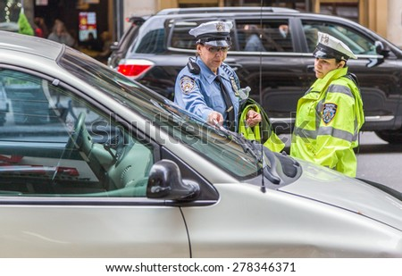 NEW YORK, New York, USA - May 22, 2013: NYPD officer writing parking ticket on May 22, 2013 in New York. The NYPD is the largest police force in the United States, with responsibilities within NYC. - stock photo