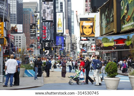 New York, New York, USA - May 1, 2011: Times Square on a bright afternoon photographed from 44th street looking uptown or north. Crowds of tourists and locals can be seen. - stock photo