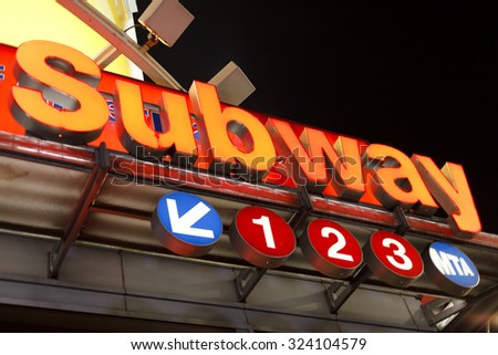 New York, New York, USA - November 9, 2011: A subway entrance sign at the corner of 33rd street and 7th avenue in Manhattan at night. - stock photo