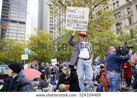 New York, New York, USA - November 3, 2011: Man holds up Occupy Wall Street sign at Zuccotti Park in Manhattan. The crowd of protestors can be seen in the background. - stock photo