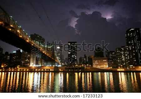 New York. Night view of the Queensborough Bridge before the storm, with lightning in the sky. - stock photo