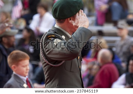 NEW YORK - NOV 11, 2014: A US Army Airborne vet wearing a green beret salutes as he passes the VIP stage during the 2014 America's Parade held on Veterans Day in New York City on November 11, 2014.