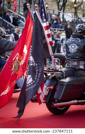 NEW YORK - NOV 11, 2014: A US vet rides a Harley Davidson motorcycle with the American, USMC, and POW / MIA Flags attached to the back during the 2014 America's Parade on Veterans Day on Nov 11, 2014. - stock photo