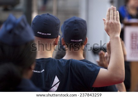 NEW YORK - NOV 11, 2014: New recruits to the US Air Force raise their right hand as they are sworn in during the 2014 America's Parade held on Veterans Day in New York City on November 11, 2014.