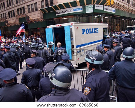 NEW YORK - NOV 17: Police stand guard after arresting Occupy Wall Street demonstrators at Beaver Street and Broad Street, on November 17, 2011 in New York City. Anti-bank marchers had blocked traffic. - stock photo