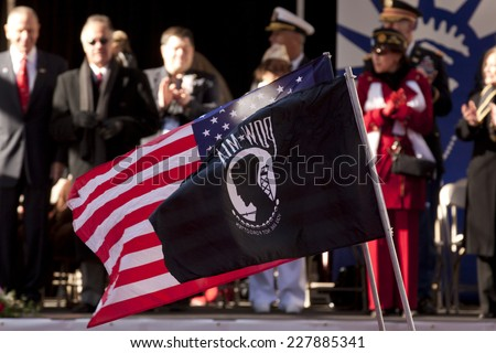 NEW YORK - NOV 11, 2013: The American Flag and POW/MIA flag wave as marchers pass the VIP viewing stand during the 2013 America's Parade held on Veterans Day in New York City on November 11, 2013. - stock photo