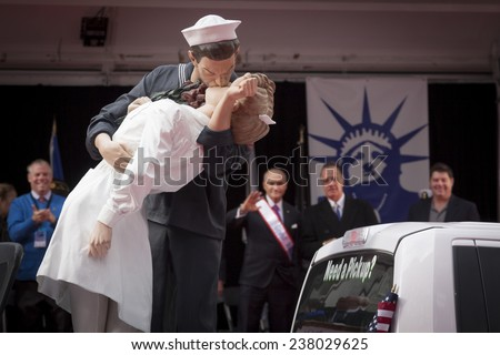 """NEW YORK - NOV 11, 2014: The sculpture of a sailor kissing a woman inspired by the """"Times Square Kiss"""" on the """"Keep the Spirit of '45 Alive!"""" float during the 2014 America's Parade on Veterans Day. - stock photo"""