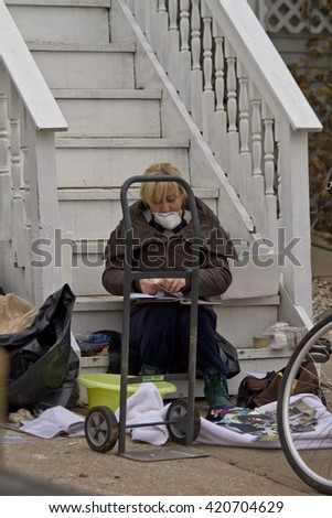 NEW YORK -NOV 12:Woman going through photographs after Hurricane Sandy in the flooded neighborhood at South Beach Staten Island area on November 10, 2012 in New York City, NY.  - stock photo