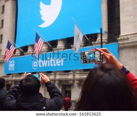 NEW YORK, NOVEMBER 7: A woman photographs the Twitter logo outside the New York Stock Exchange in New York City, November 7, 2013. Twitter was debuting as a publicly traded company. - stock photo