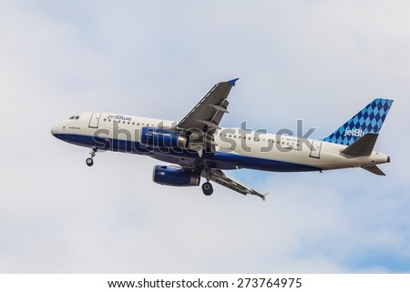 NEW YORK - NOVEMBER 3: Airbus A320 JetBlue approaches JFK Airport in New York, NY on November 3, 2013. A320 was the first narrow body airliner from Airbus and the biggest competition to Boeing 737. - stock photo