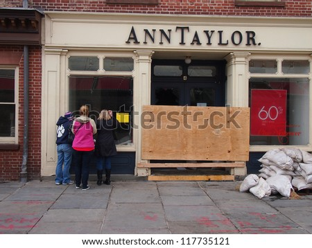 NEW YORK, NOVEMBER 3: Passersby inspect a damaged Ann Taylor store at the Seaport in New York City, November 3, 2012. Lower Manhattan was seriously damaged by flooding from Hurricane Sandy. - stock photo