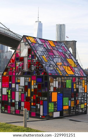 NEW YORK  - NOVEMBER 9: Stained glass sculpture by Tom Fruin under Brooklyn Bridge on November 9, 2014. Sculptor Tom Fruin installed his famous plexiglass house, Kolonihavehus, in Brooklyn Bridge Park - stock photo