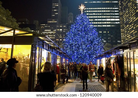 NEW YORK - NOVEMBER 30: Tourists and shoppers visit the Shops at Bryant Park near the Christmas tree on November 30, 2012 in  New York City. - stock photo