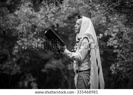NEW YORK - NOVEMBER 3: Ultra Orthodox Jewish man praying in the forest in the morning. Jewish men pray morning prayer called Shacharis every day as observed on November 3 2015 - stock photo