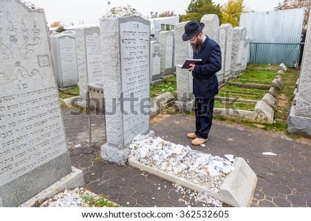 NEW YORK - NOVEMBER 6: Ultra Orthodox Jewish man prays at graveside of Rebbetzin Chaya Mushka, the Lubavitcher Rebbe's wife at Montefiore Cemetery in New York, NY on November 6, 2015. - stock photo