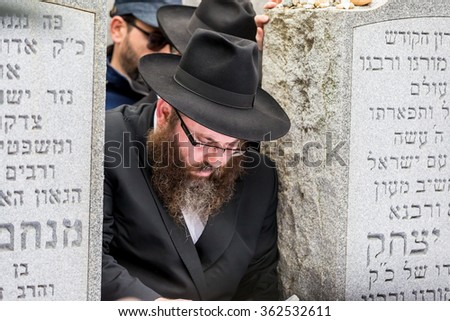 NEW YORK - NOVEMBER 6: Ultra Orthodox Jewish man prays at the Ohel in New York, NY on November 6, 2015. The Ohel is where Rabbi Menachem Schneerson was laid to rest next to Rabbi Yosef Y. Schneersohn. - stock photo