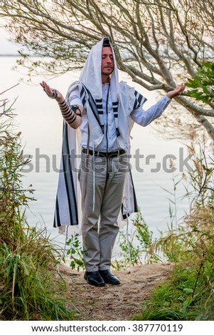 NEW YORK - NOVEMBER 3: Ultra Orthodox Jewish man prays in the forest on November 3, 2015 in New York, NY. Jewish men are obligated to pray three times daily at certain times. - stock photo