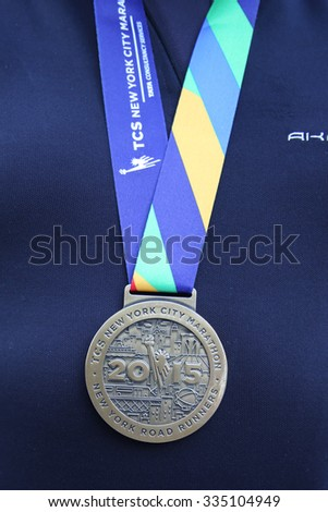 NEW YORK - NOVEMBER 3, 2015: Unidentified 2015 New York City Marathon runner wears medal in Manhattan. The TCS New York City Marathon is one of the world's most iconic races - stock photo