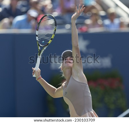 NEW YORK, NY - AUGUST 31, 2014: Caroline Wozniacki of Denmark serves ball during 4th round match against Maria Sharapova of Russia at US Open tennis tournament in Flushing Meadows USTA Tennis Center - stock photo
