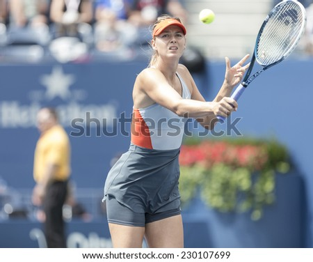 NEW YORK, NY - AUGUST 31, 2014: Maria Sharapova of Russia returns ball during 4th round match against Caroline Wozniacki of Denmark at US Open tennis tournament in Flushing Meadows USTA Tennis Center - stock photo