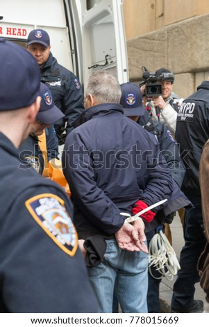 New York, NY - December 19, 2017: Police makes arrest of protesters during rally against tax bill in US Congress in front of New York Stock Exchange