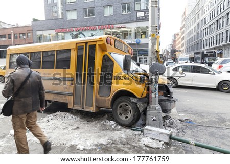 NEW YORK, NY - FEBRUARY 12, 2014: Passerby examines school bus accident on the corner of 6th avenue and 18th street in Manhattan - stock photo