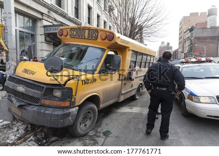 NEW YORK, NY - FEBRUARY 12, 2014: Police officer examines school bus accident on the corner of 6th avenue and 18th street in Manhattan