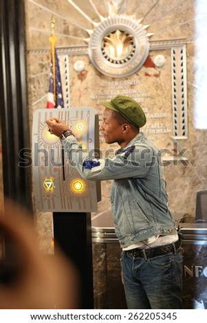 "NEW YORK, NY â?? MARCH 20, 2015: Pharrell Williams '""flips the switch"" at the Empire State Building Lighting ceremony  to mark the United Nationsâ?? International Day of Happiness. The building will be lit in yellow to mark the occasion."