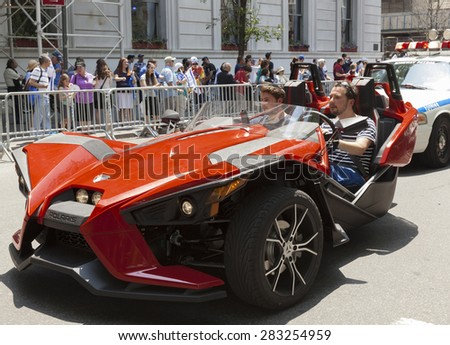 NEW YORK, NY - MAY 31, 2015: Atmosphere during Celebrate Israel Parade on 5th avenue in Manhattan with spectator riding Polaris Slingshot motorcycle - stock photo