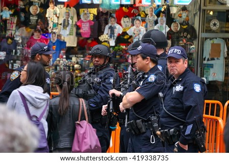 New York, NY - May 10, 2016: NYPD counter terrorism officers patrol famous Time Square where millions of tourists visit Manhattan. Site of the ball dropping for New Years Eve celebration - stock photo