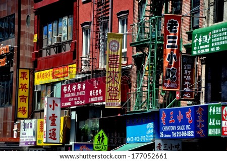 New York, NY - May 2, 2011:  Shop and business signs, mostly written in Chinese characters, hang from tenenment buildings on East Broadway in Chinatown - stock photo