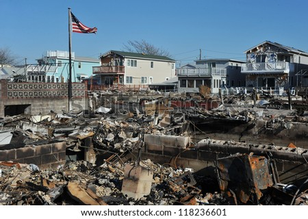 NEW YORK, NY - NOVEMBER 09: An American flag flies from the burned house in a damaged area November 9, 2012 in the Breezy Point part of Far Rockaway in the Queens borough of NY. - stock photo