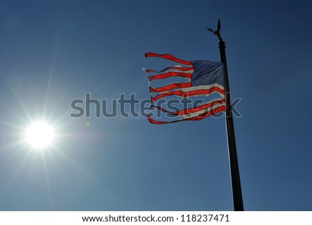 NEW YORK, NY - NOVEMBER 09: An American ripped flag flies from the front yard of a house in a damaged area November 9, 2012 in the Breezy Point part of Far Rockaway in the Queens borough of NY. - stock photo