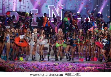 NEW YORK, NY - NOVEMBER 09: Models pose on the runway with Nicki Minaj, Kanye West and members of Maroon 5 during the 2011 Victoria's Secret Fashion Show at the Armory on November 9, 2011 in NYC. - stock photo