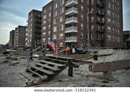 NEW YORK, NY - NOVEMBER 09: The destroyed boardwalk and a tattered American flag following Superstorm Sandy at Rockaway Beach on November 9, 2012 in the Queens borough of New York City. - stock photo