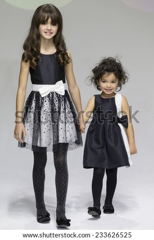 NEW YORK, NY - OCTOBER 19: Adrianna (L) and Olivia Perez (R) walk the runway during the Ruum preview at petitePARADE - Kids Fashion Week at Bathhouse Studios - stock photo
