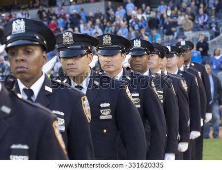 New York, NY - October 25, 2015: NYC police officers salute before match between NYC FC & New England Revolution at Yankee Stadium - stock photo