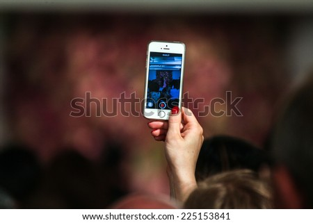 NEW YORK, NY - SEPTEMBER 09: A guest holding a cellphone and making pictures at the Oscar De La Renta fashion show during Mercedes-Benz Fashion Week Spring 2015 on September 9, 2014 in New York City. - stock photo