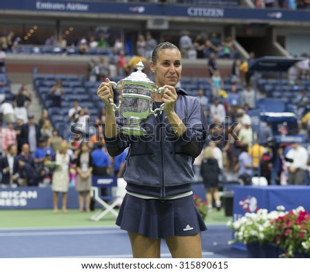 New York, NY - September 12, 2015: Flavia Pennetta of Italy holds trophy after winning final match against Roberta Vinci of Italy at US Open Championship - stock photo