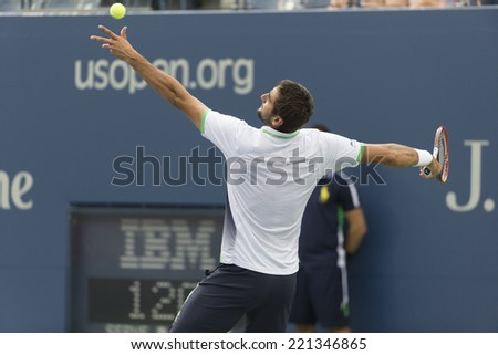 NEW YORK, NY - SEPTEMBER 6, 2014: Marin Cilic of Croatia serves ball during semifinal match against Roger Federer of Switzerland at US Open championship in Flushing Meadows USTA Tennis Center - stock photo