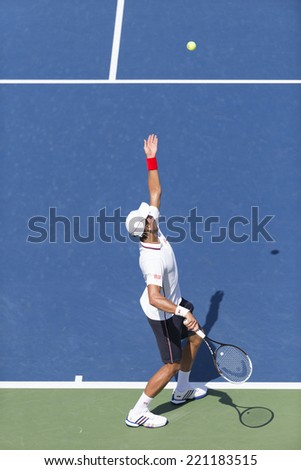 NEW YORK, NY - SEPTEMBER 6, 2014: Novak Djokovic of Serbia serves ball during semifinal match against Kei Nishikori of Japan at US Open championship in Flushing Meadows USTA Tennis Center - stock photo