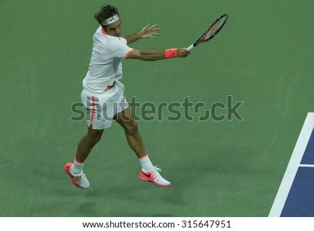 New York, NY - September 11, 2015: Roger Federer of Switzerland returns ball during semifinal match against Stan Wawrinka of Switzerland at US Open Championship - stock photo