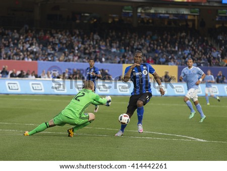 New York, NY USA - April 27, 2016: Goalkeeper Josh Saunders of NYC FC saves the ball from Didier Drogba (11) of Montreal during MLS game NYC FC against Montreal Impact at Yankee Stadium - stock photo