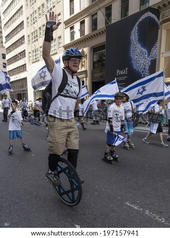 New York, NY USA - June 01, 2014: Atmosphere with man riding unicycle imbedded Magen David during 50th annual Israeli Day parade on 5th Avenue in Manhattan