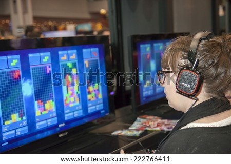 New York, NY, USA - October 10 2014: Comic Con attendee plays Tetris Ultimate during Comic Con 2014 at The Jacob K. Javits Convention Center in New York City - stock photo