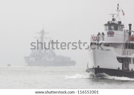 NEW YORK-OCT 9: A Statue Cruise ferry returns to port as the USS Michael Murphy (DDG 112) departs New York Harbor in rain and fog fully commissioned into active service in New York on October 9, 2012. - stock photo